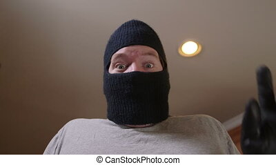 Man wearing ski mask falling down backwards close up