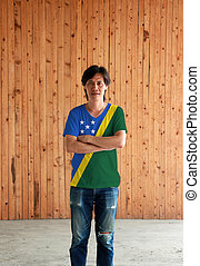 Man wearing Solomon Islands flag color shirt and cross one's arm on wooden wall background.