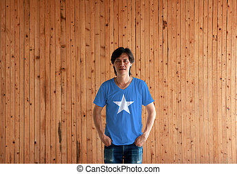 Man wearing Somalia flag color shirt and standing with two hands in pant pockets on the wooden wall background.