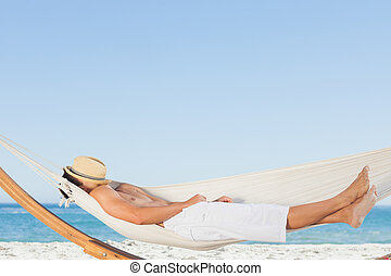 Man wearing straw hat relaxing in a hammock on the beach on...