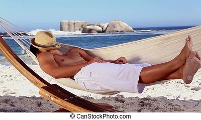 Man wearing straw hat relaxing in a hammock on the beach