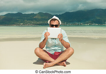 man wearing sunglasses hiding behind tablet while sitting...
