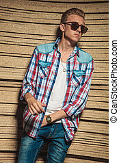 man wearing sunglasses posing with hand in pocket