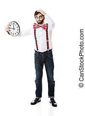 Man wearing suspenders holding big clock.