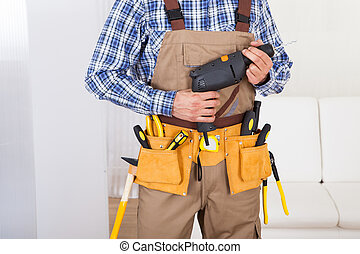 Man Wearing Tool Belt At Home - Midsection of young man...