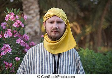 Man wearing traditional bedouin clothing in Sahara desert....