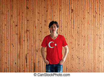 Man wearing Turkey flag color shirt and standing with two hands in pant pockets on the wooden wall background.