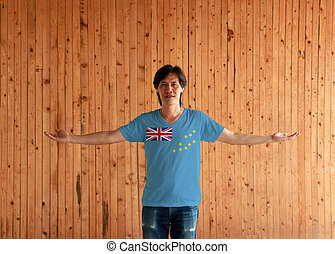 Man wearing Tuvalu flag color shirt and standing with arms wide open on the wooden wall background.
