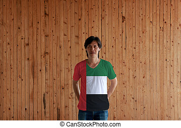 Man wearing UAE flag color of shirt and standing with crossed behind the back hands on the wooden wall background.