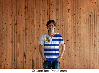 Man wearing Uruguay flag color shirt and standing with two hands in pant pockets on the wooden wall background.