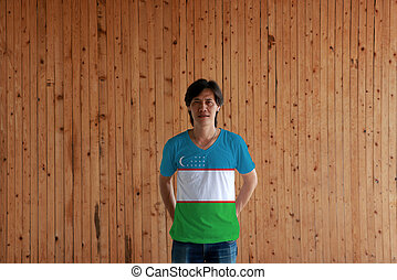 Man wearing Uzbekistan flag color of shirt and standing with crossed behind the back hands on the wooden wall background.