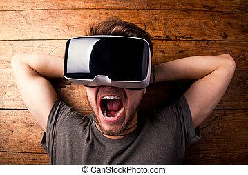 Man wearing virtual reality goggles. Studio shot, wooden...