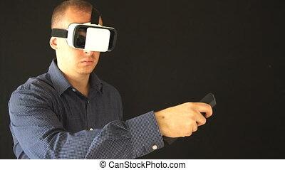 Man wearing virtual reality goggles. Studio shot, black...