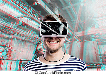Man wearing virtual reality goggles. Welding factory.