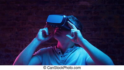 Front view close up of a young Caucasian man wearing a VR headset and looking around, lit with pink and blue light on a black background