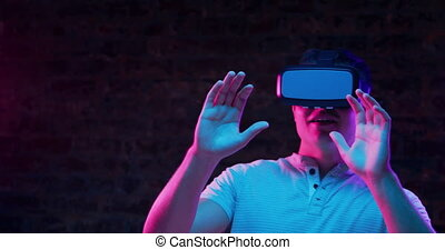 Front view close up of a young Caucasian man wearing a VR headset, smiling and looking around and moving, with both hands raised in front of him as if avoiding things, lit with pink and blue light on a black background