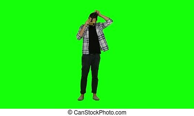 Man wearing VR headset. Using gestures with hands. Green screen