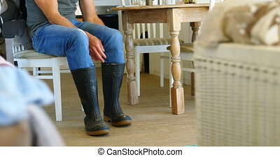 Man wearing wellington boot at home 4k - Low section of man...