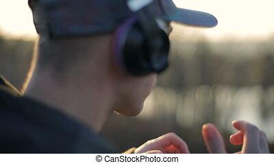 Man Wears Headphones Against Sunset