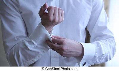 Man wears shiny cufflinks. Man in a white shirt dress cufflinks, young men are ready for the ceremony, wedding accessories for stylish men, groom wears stylish cufflinks close up,man wears white shirt and cufflinks, men wear white shirt details, close up