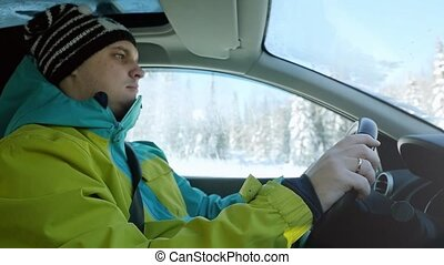 Man wears ski suit drivers the car in slow motion on winter landscape outdoors. 1920x1080
