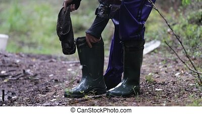 man wears wet boots in the forest close-up