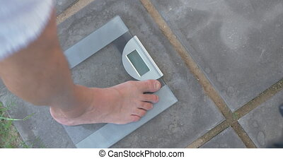 Man weighing himself on bathroom scales - High angle shot of...