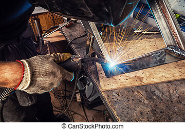 man weld a metal welding machine - A young man welder in a ...