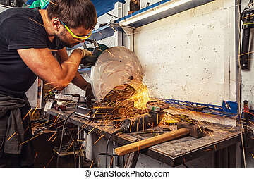 man welder cuts a metal with a circular saw