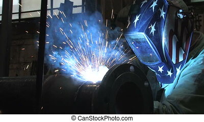 A worker welding in a factory as sparks fly (includes audio)