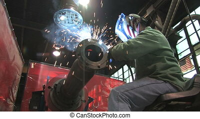 Low angle of a worker welding in a factory as sparks fly (includes audio)