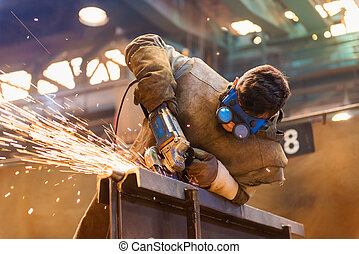 Man welding - Young man with protective goggles welding in a...