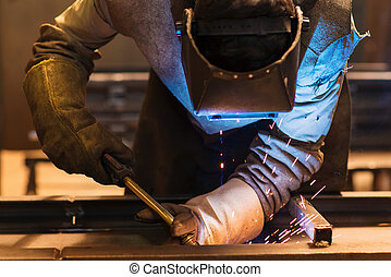 Man welding - Young man with protective mask welding in a ...