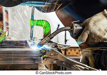 man welds a metal welding machine