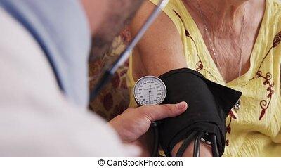 man, werkende , in, hospice, en, het meten van bloeddruk, van, vrouw