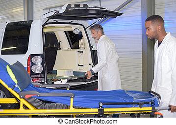 Man wheeling empty stretcher to hospital car