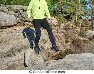 Man while jumping during a trail running in the mountains