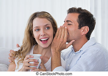 Man whispering secret into a cheerful young womans ear