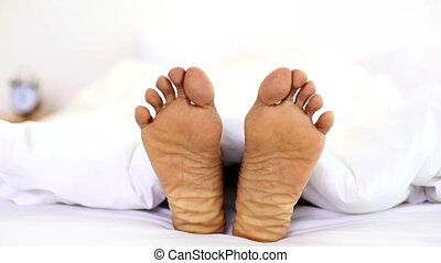 Man wiggling his toes under the covers at home in bedroom