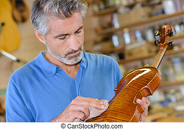 man wiping a violin