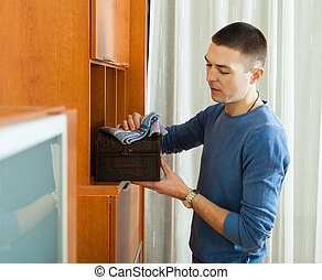 man wiping dust from wooden chest at home
