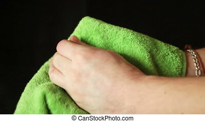 Man wiping his hands with a green towel.black background