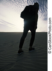 man with a backpack walking in the desert - a young...