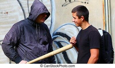 Man with a baseball bat talking
