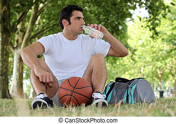 Man with a basketball and bottle of water