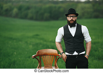 man with a beard, thinking in the field near chair