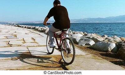 Man with a bicycle near the seaside