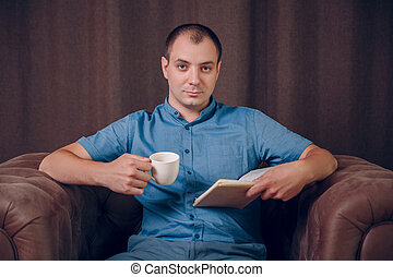 man with a book and a coffee cup in his hands sitting in an armchair and reading. Psychologist