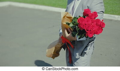 man with a bouquet of roses waits for a girl, romantic or first date, proposal to marriage