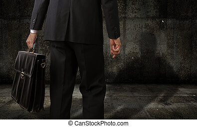 Man olding a suitcase in a dark room
